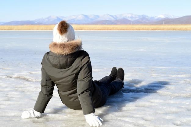 Vrouw in warme kleren zittend op het ijs en kijken naar besneeuwde bergen