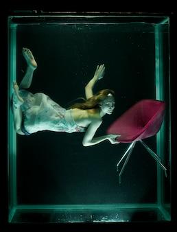 Vrouw in water met een rode stoel