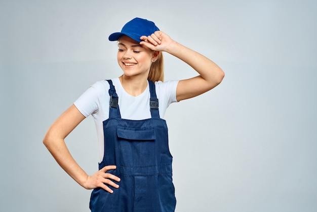 Vrouw in werk uniform en blauwe pet op een lichte achtergrond.