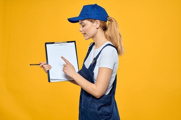 Vrouw in werk uniform met documenten over koeriersdienst op gele achtergrond