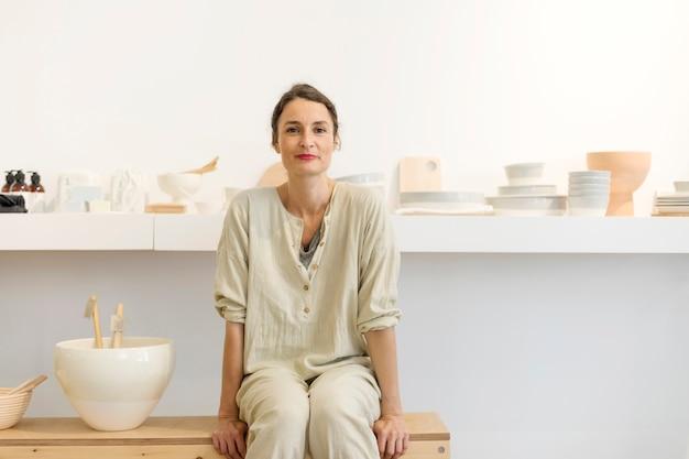 Vrouw in werkkleding in haar atelier door tafel met handgemaakte items