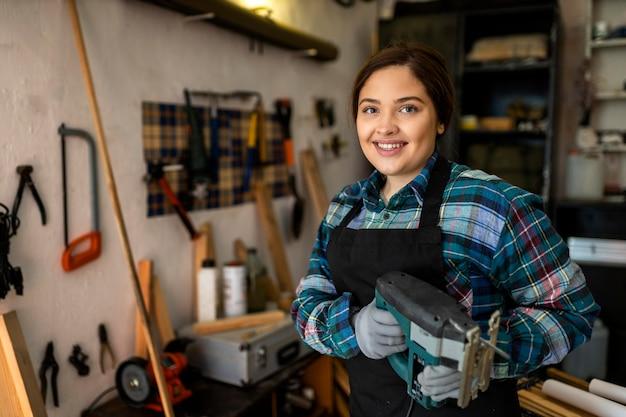 Vrouw in werkplaats met tools dor repareren