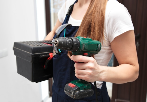 Vrouw in werkuniform in het huis met een schroevendraaier en andere apparatuur