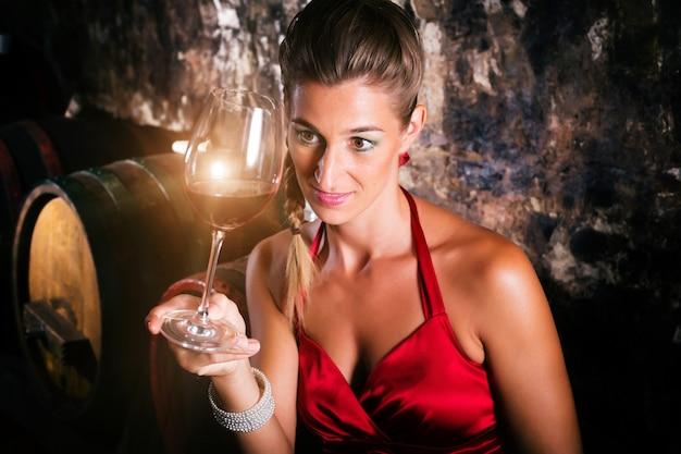 Vrouw in wijnkelder met vaten het proeven