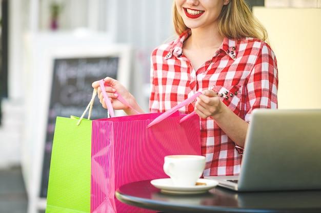 Vrouw in winkelcentrum met tassen. maniermeisje die in wandelgalerij verrast op shopwindow achtergrond kijken.