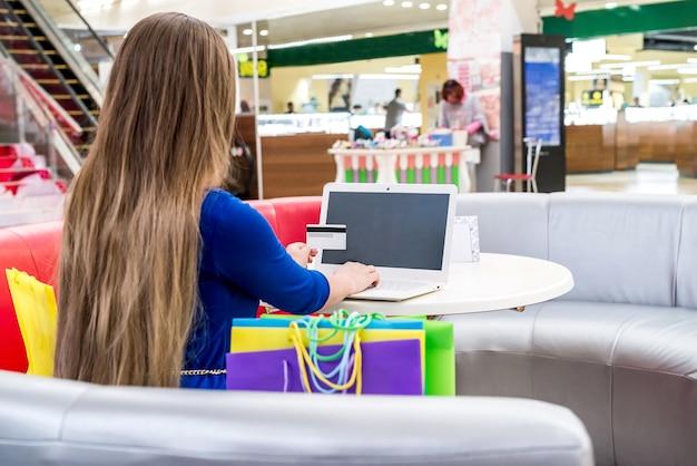 Vrouw in winkelcentrum online winkelen met laptop doen
