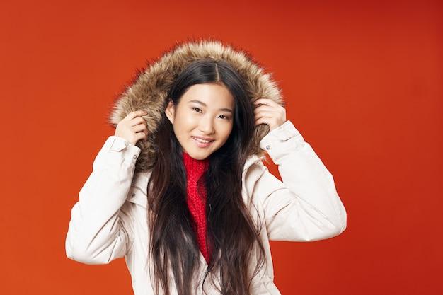 Vrouw in winter jas levensstijl elegante stijl mode rode achtergrond