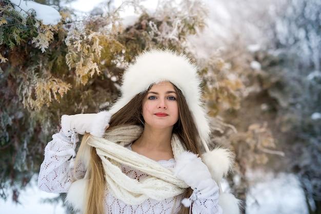 Vrouw in winter park poseren in bontmuts en sjaal
