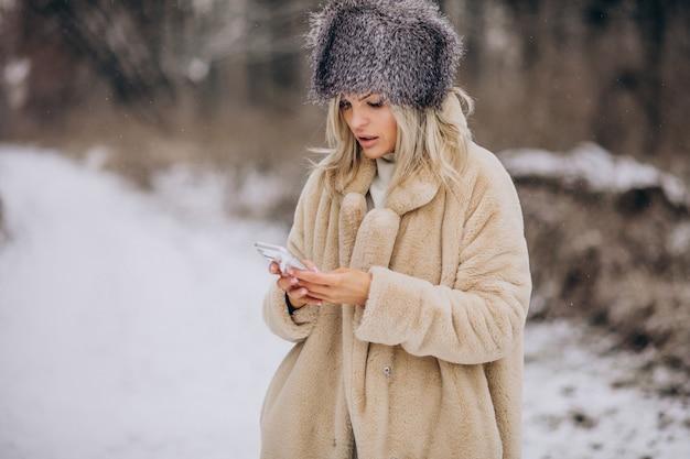 Vrouw in winterjas wandelen in park vol sneeuw praten aan de telefoon
