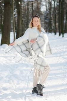 Vrouw in winterkleren in besneeuwde park
