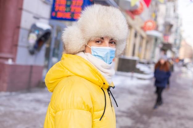 Vrouw in winterkleren op een koude dag te wachten op een bus bij een bushalte
