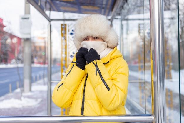 Vrouw in winterkleren op een koude dag te wachten op een bus bij een bushalte Gratis Foto