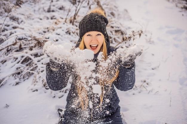 Vrouw in winterkleren spelen met sneeuw