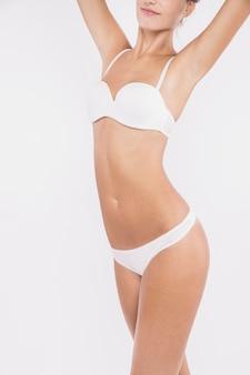 Vrouw in wit ondergoed die zich op witte achtergrond bevinden