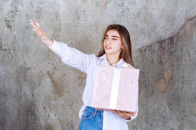 Vrouw in wit overhemd die een roze geschenkdoos vasthoudt omwikkeld met een wit lint, haar partner opmerkt en hem vraagt om het te komen ontvangen.