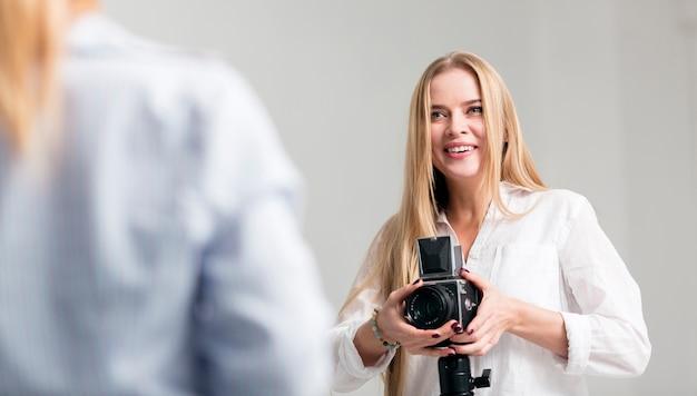Vrouw in wit overhemd die haar camera met behulp van