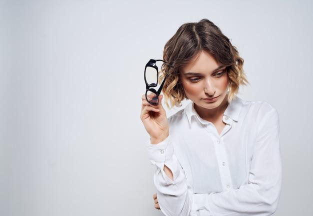 Vrouw in wit overhemd emotie kantoor studio lichte achtergrond zakenvrouw
