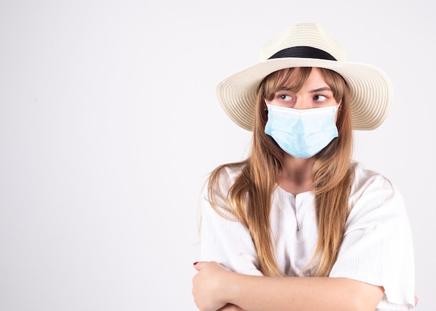 Vrouw in wit overhemd en hoed die masker draagt