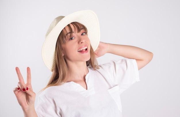 Vrouw in wit overhemd en hoed