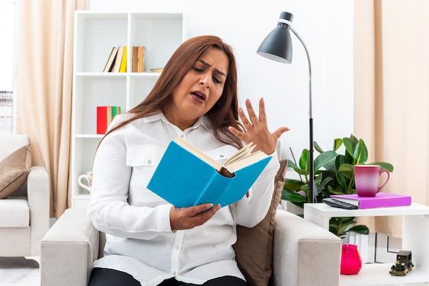 Vrouw in wit overhemd en zwarte broek die een boek leest en er emotioneel en geïntrigeerd uitziet terwijl ze op de stoel zit in een lichte woonkamer