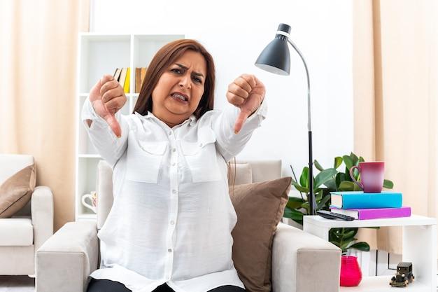 Vrouw in wit overhemd en zwarte broek die met een boos gezicht kijkt en ontevreden is met duimen naar beneden zittend op de stoel in een lichte woonkamer