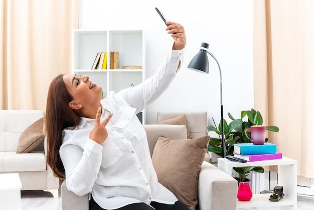 Vrouw in wit overhemd en zwarte broek doet selfie met smartphone gelukkig en positief lachend met v-teken zittend op de stoel in lichte woonkamer