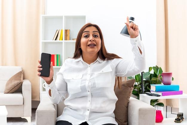 Vrouw in wit overhemd en zwarte broek met smartphone die lacht en wijsvinger laat zien met een nieuw idee zittend op de stoel in een lichte woonkamer