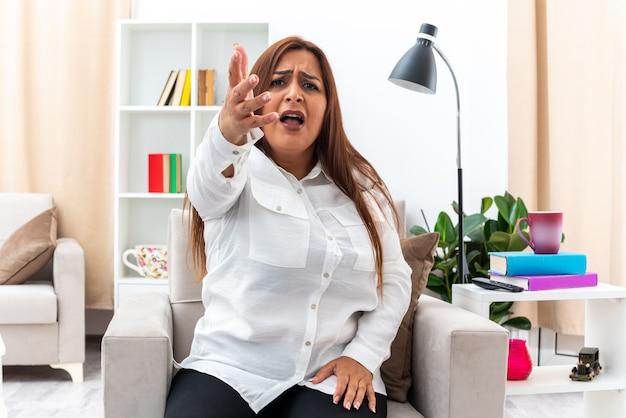Vrouw in wit overhemd en zwarte broek zittend op de stoel die er ontevreden en verward uitziet met opgeheven arm in ongenoegen en verontwaardiging in lichte woonkamer