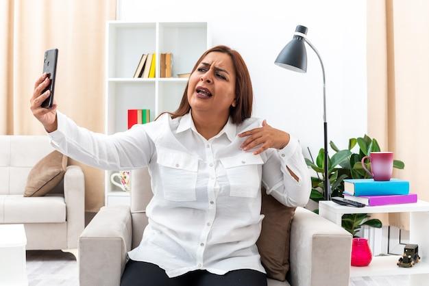 Vrouw in wit overhemd en zwarte broek zittend op de stoel selfie te maken met smartphone en verward in lichte woonkamer in