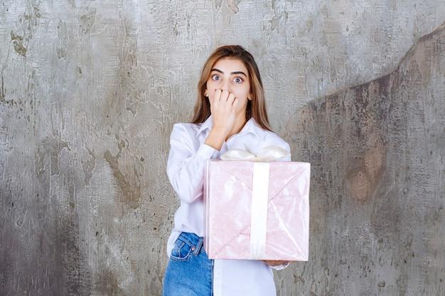 Vrouw in wit overhemd met een roze geschenkdoos omwikkeld met wit lint en ziet er bang of doodsbang uit.