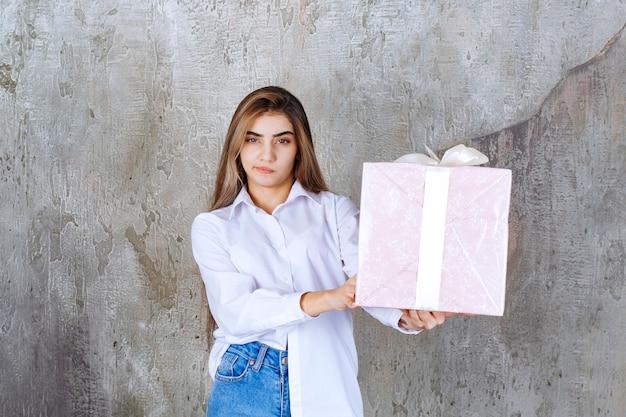 Vrouw in wit overhemd met een roze geschenkdoos omwikkeld met wit lint en ziet er verward en aarzelend uit.