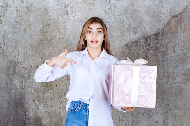 Vrouw in wit overhemd met een roze geschenkdoos omwikkeld met wit lint.