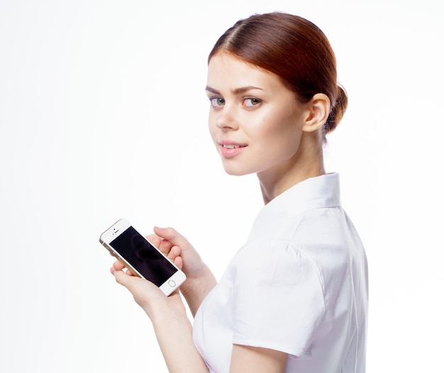 Vrouw in wit overhemd met telefoon in handen technologie internetcommunicatie. hoge kwaliteit foto