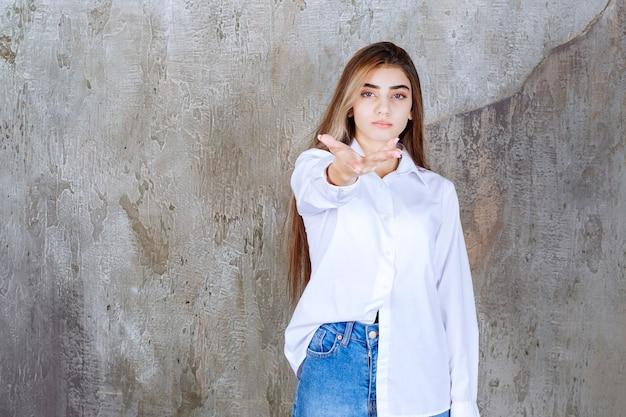 Vrouw in wit overhemd staat op een betonnen muur en merkt de persoon rond.
