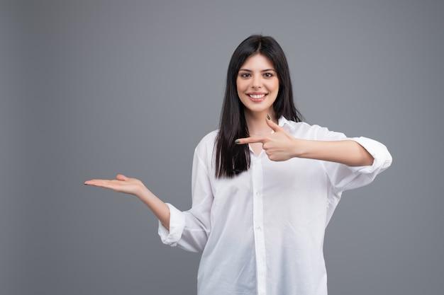 Vrouw in wit shirt wijzend op copyspace op haar hand geïsoleerd over grijs