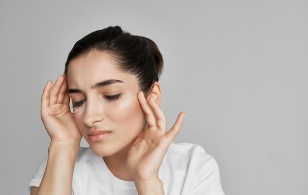 Vrouw in wit t-shirt bijgesneden weergave gezondheidsprobleem hoofdpijn.
