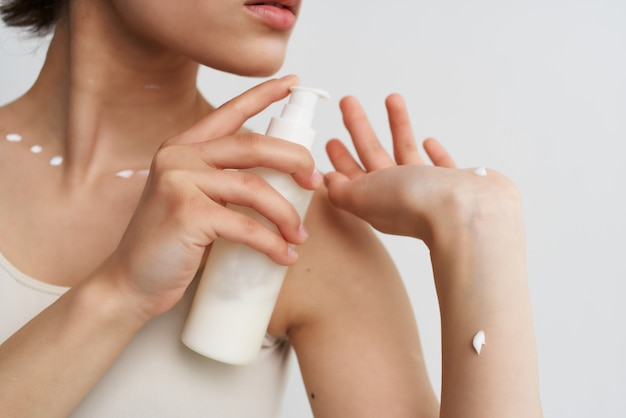 Vrouw in wit t-shirt brengt crème aan op huidclose-up