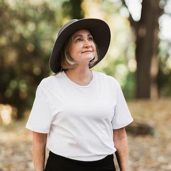 Vrouw in wit t-shirt die de schoonheid van de aard waardeert