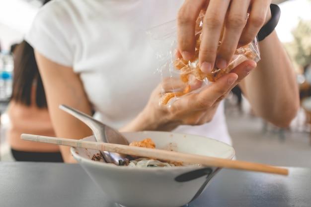 Vrouw in wit t-shirt eet varkenszwoerd of varkensvlees knetteren met thaise noedels.