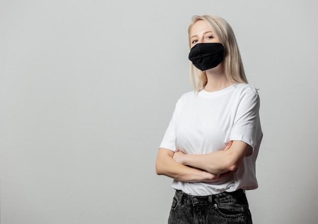 Vrouw in wit t-shirt en zwart gezichtsmasker op witte muur