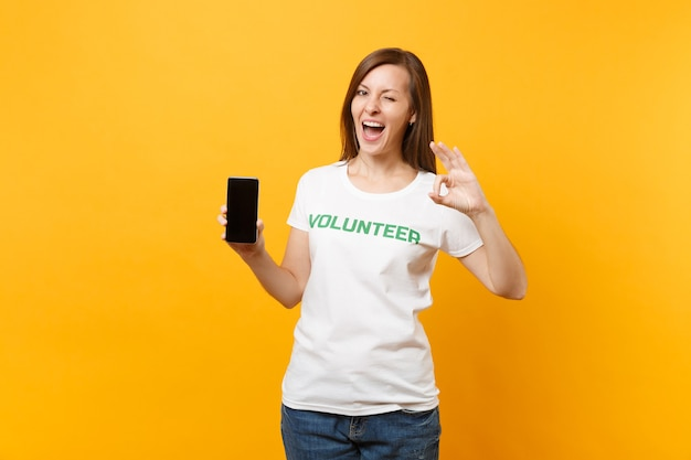 Vrouw in wit t-shirt geschreven inscriptie groene titel vrijwilliger houdt mobiele telefoon met leeg leeg scherm geïsoleerd op gele achtergrond. vrijwillige gratis hulp, liefdadigheidswerkconcept.