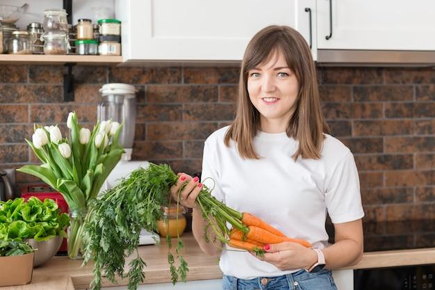 Vrouw in wit t-shirt met verse wortelen in loft keuken thuis close-up. raw food-dieet en gezond eten concept. goede oogst, boerenmeisje