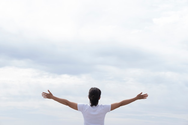 Vrouw in wit t-shirt verhogen haar armen met uitzicht op de zee