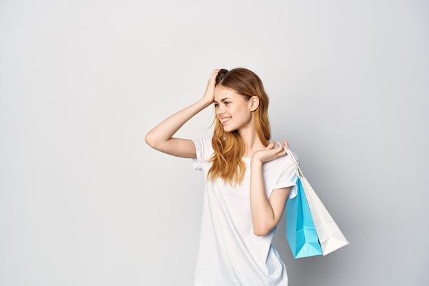 Vrouw in wit t-shirtpakket in handen cadeau winkelen lichte achtergrond