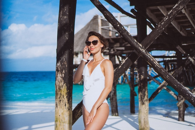 Vrouw in wit zwemmend kostuum door de oceaan die telefoon met behulp van