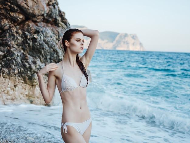 Vrouw in wit zwempak oceaan rotsen poseren bikini posing