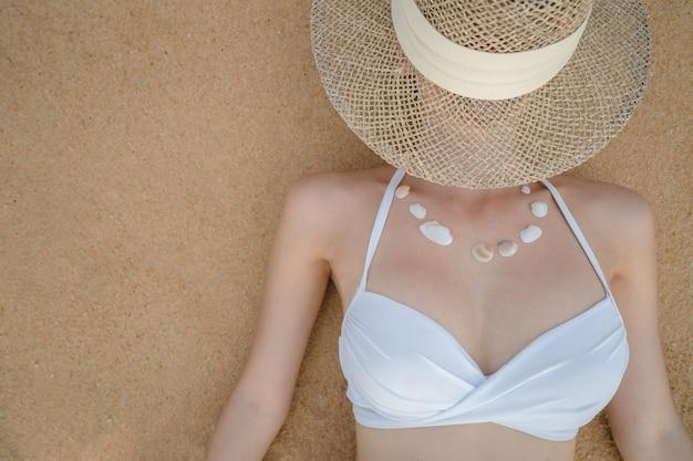 Vrouw in witte bikini die op zandstrand ligt en ketting maakt van zeeschelp, strohoed die haar gezicht bedekt.