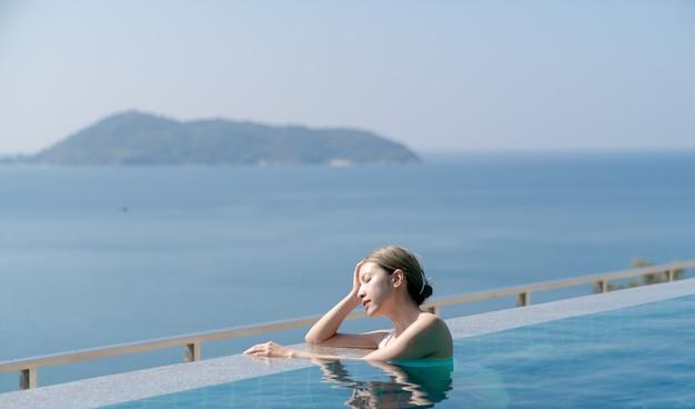 Vrouw in witte bikini ontspannen aan de rand van een overloopzwembad met uitzicht over de blauwe zee.