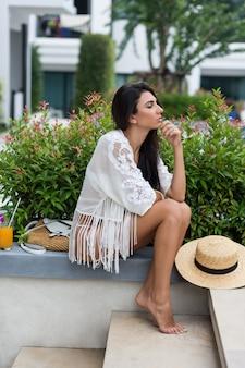 Vrouw in witte bikini poseren in modern hotel in thailand stijlvolle boho strandkleding dragen