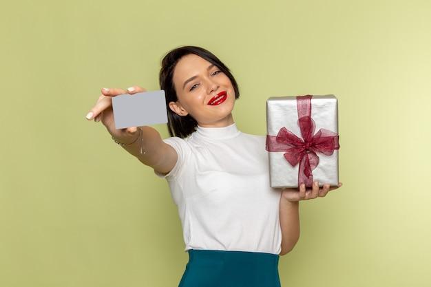 Vrouw in witte blouse en groene rok met grijze kaart en huidige doos